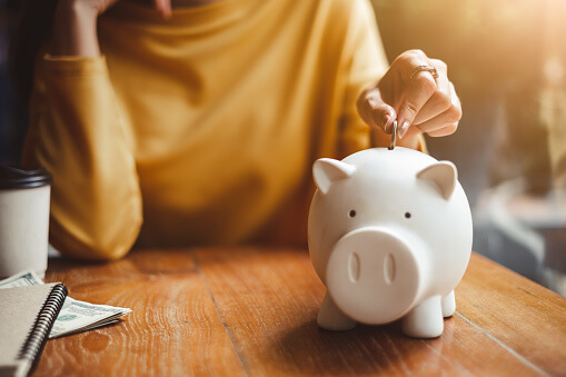 Image of woman putting money in piggy bank